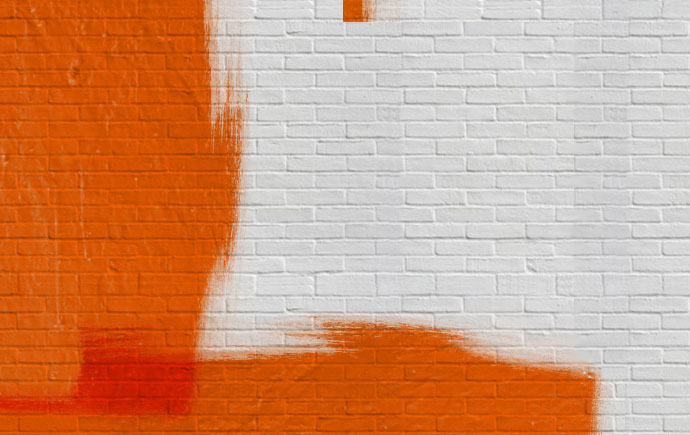 Brick wall with orange and white pain on