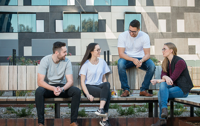 four students sitting on a bench talking