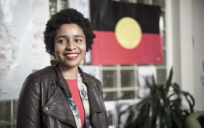 Female student standing by Aboriginal flag