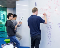 Photo of Students working at a whiteboard in one of our many study areas.