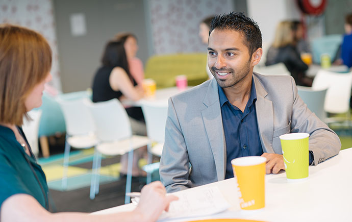 Staff talk over coffee
