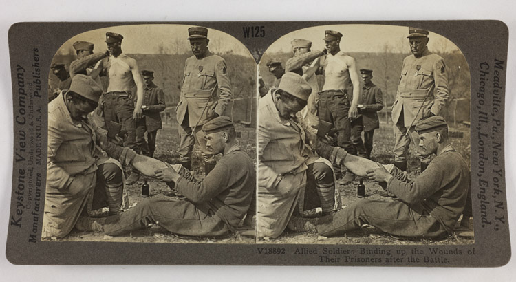 Allied soldiers binding up the wounds of their prisoners after the battle