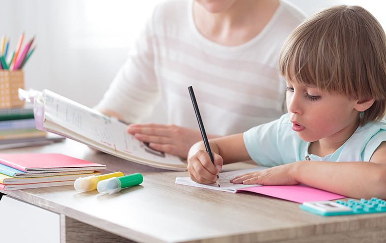 a child drawing while mother looks on